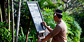 A Balinese waiter writing the daily menu on a blackboard in a tropical setting. Singaraja, Bali.