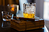 A stillife of a glass of whisky with a cigar set upon an old book.\nShot in Algarve, Portugal.