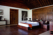 An interior shot of a Bali bedroom, designed and built in hardwood, with a carved door used as a headboard.