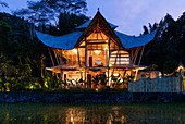 Evening shot of a lit bamboo house, pagoda style, set in a ricefield in Bali