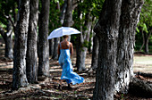 Woman in a blue dress swirling a white umbrella whilewalking in the woods.