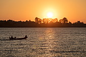 Silhouette of longtail fishing boat on the Mekong at sunset, near Preah Prosop, Mekong River, Kandal, Cambodia, Asia