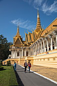 Young couple on walkway in front of Throne Room building within the Royal Palace complex, Phnom Penh, Cambodia, Asia