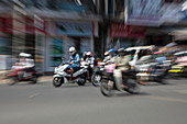 Zoomed image of people on mopeds on busy street, Phnom Penh, Cambodia, Asia