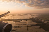 Aerial view from wing of a Vietnam Airlines Airbus A-320 airplane overlooking flooded fields at sunset, near Siem Reap, Siem Reap Province, Cambodia, Asia
