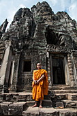 Buddhist monk stands proudly in front of the Bayon Temple in Angkor Thom, Angkor Wat, near Siem Reap, Siem Reap Province, Cambodia, Asia