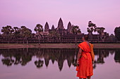 Buddhist monk stands by the moat and admires Angkor Wat temple at sunset, Angkor Wat, near Siem Reap, Siem Reap Province, Cambodia, Asia