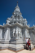 Young couple admires the ornate decoration with three-headed elephants on the stupa on Mount Phnom Oudong, Oudong (Udong), Kampong Speu, Cambodia, Asia