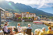 View of harbour and architecture on a sunny day, Malcesine, Lake Garda, Province of Verona, Veneto, Italian Lakes, Italy, Europe