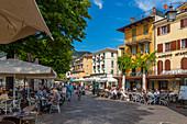 View of cafes and visitors on the promenade on a sunny day, Garda, Lake Garda, Province of Verona, Veneto, Italian Lakes, Italy, Europe