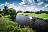 The Ems-Jade Canal with motorboat at Reepsholt, Friedeburg, Wittmund, East Frisia, Lower Saxony, Germany, Europe