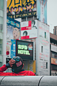 Youngster leans against a bridge in Dotonbori. Osaka, Japan