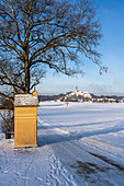 Andechs Monastery in a snowy winter landscape with a station path to the Friedrichskapelle, Andechs, Bavaria, Germany.