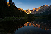 The Fusine lake is of glacial origin and one of the most beautiful in the julian Alps. In the background, the mountain group of Mount Mangart which marks the border with Slovenie. Italy.