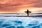 Rear view of  a woman standing on a beach holding a surfboard, looking out to sea with a sunset in the background.