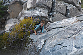 A woman climbing up a rocky slope with ropes.