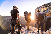 A group of people on a rocky outcrop watching a sunset.