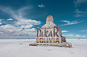 Large rock sign of Dakar Bolivia in the salt flats below a blue sky with white clouds.