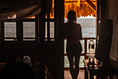 Rear view, a woman in a doorway looking out over sea.