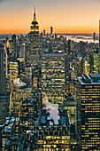 View of Manhattan skyline with illuminated skyscrapers at sunset, New York City