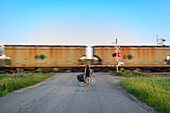 Cyclist waiting for train ahead to pass, Ontario, Canada