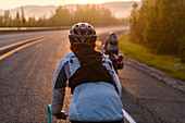 Cyclists on road at sunset, Ontario, Canada