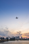 A plane arriving at the City of London airport with the Victoria Dock and skyline of the financial district, Docklands, London, England, United Kingdom, Europe