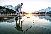Front view of ice hockey player on cracked surface of frozen Lake Sils, Engadine, Graubunden canton, Switzerland, Europe