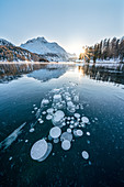 Ice bubbles trapped in frozen Lake Sils at sunset with Piz Da La Margna in background, Engadine, Graubunden canton, Switzerland, Europe