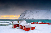 Winter sunset over the Arctic sea and fishermen cabins in the snow, Sorvaer, Soroya Island, Hasvik, Troms og Finnmark, Norway, Scandinavia, Europe