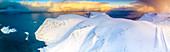 Aerial view of sunrise on snow capped mountains and blue arctic sea, Sorvaer, Soroya Island, Hasvik, Troms og Finnmark, Arctic, Norway, Scandinavia, Europe