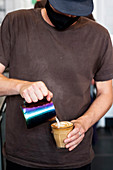 Close up of male barista wearing face mask pouring cafe latte.