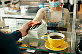 Woman in a face mask behind cafe counter with safety screen, offering a contactless payment terminal to a customer
