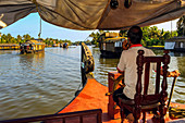 Captain on phone and steering houseboat through the backwaters on a popular backwater cruise, Alappuzha (Alleppey), Kerala, India, Asia