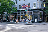 Group of People sitting on Sidewalk in front of White Horse Tavern, New York City, New York, USA