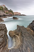a long exposure to capture a cloudy sunset on the winding cliffs of Tellaro, municipality of Lerici, La Spezia province, Liguria district, Italy, Europe