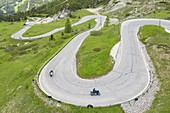 aerial view taken from the drone of two motorcyclists traveling the curvy road of the Pordoi Pass during a summer day, Fassa Valley, Dolomiti, municipality of Canazei, Trento province, Trentino Alto Adige district, Italy, Europe