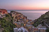 a panoramic view of the village of Manarola during a colorful late spring sunset, National Park of Cinque Terre, Unesco World Heritage Site, municipality of Riomaggiore, La Spezia province, Liguria district, Italy, Europe