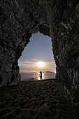 a night landscape photographer is photographed from inside a cave on a beach, municipality of Ameglia, La Spezia province, Liguria district, Italy, Europe