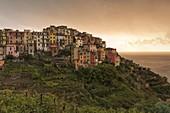 the warm light of an autumn sunset envelops the village of Corniglia, national park of Cinque Terre, Unesco World Heritage Site, municipality of Vernazza, La Spezia province, Liguria district, Italy, Europe