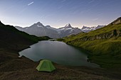 a mountaineer rests in a tent, during a clear summer night at Bachalpsee, Grindelwald, Oberland, Canton of Berne, Switzerland, Europe