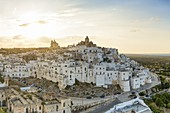 """aerial view of Ostuni, so called """"the white city"""", during a summer sunset, municipality of Ostuni, Brindisi province, Apulia district, Italy, Europe"""