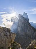 A man observes sunrise at Seceda, Gruppo delle Odle, Dolomiti di Gardena, Bolzano, Trentino Alto Adige, Italy, Southern Europe