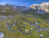 Aerial view of the Alpe Pedriola and it's winding rivers with the east face of Mount Rosa massif in the back. Macugnaga, Anzasca Valley, Verbano Cusio Ossola province, Piedmont, Italy, Europe.
