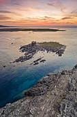 Aerial view of the small island and the medieval tower of La Pelosa and Isola Piana at dawn, Stintino, Asinara Gulf, Sassari district, Sardinia, Italy.