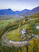 The Vigezzina-Centovalli train passes over a round shape curve of the railway in the autumnal colors of foliage near Trontano. Valle Vigezzo, val d'Ossola, Verbano Cusio Ossola, Piedmont, Italy.