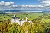 Schwangau, district Ostallgäu, Swabia, Bavaria, Germany, Europe. Autumn at the Neuschwanstein castle, in the background the Forggen lake
