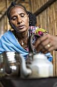 Woman preparing tea and coffee, Berhale, Afar Region, Ethiopia, Africa