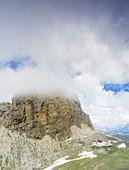 Aerial panoramic of clouds over Denti di Terrarossa (Rosszahne) and Alpe di Tires hut, Dolomites, Trentino Alto Adige, Italy