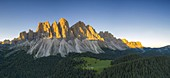 Odle peaks lit by sunrise surrounded by green woods in summer, Val di Funes, South Tyrol, Bolzano province, Dolomites, Italy